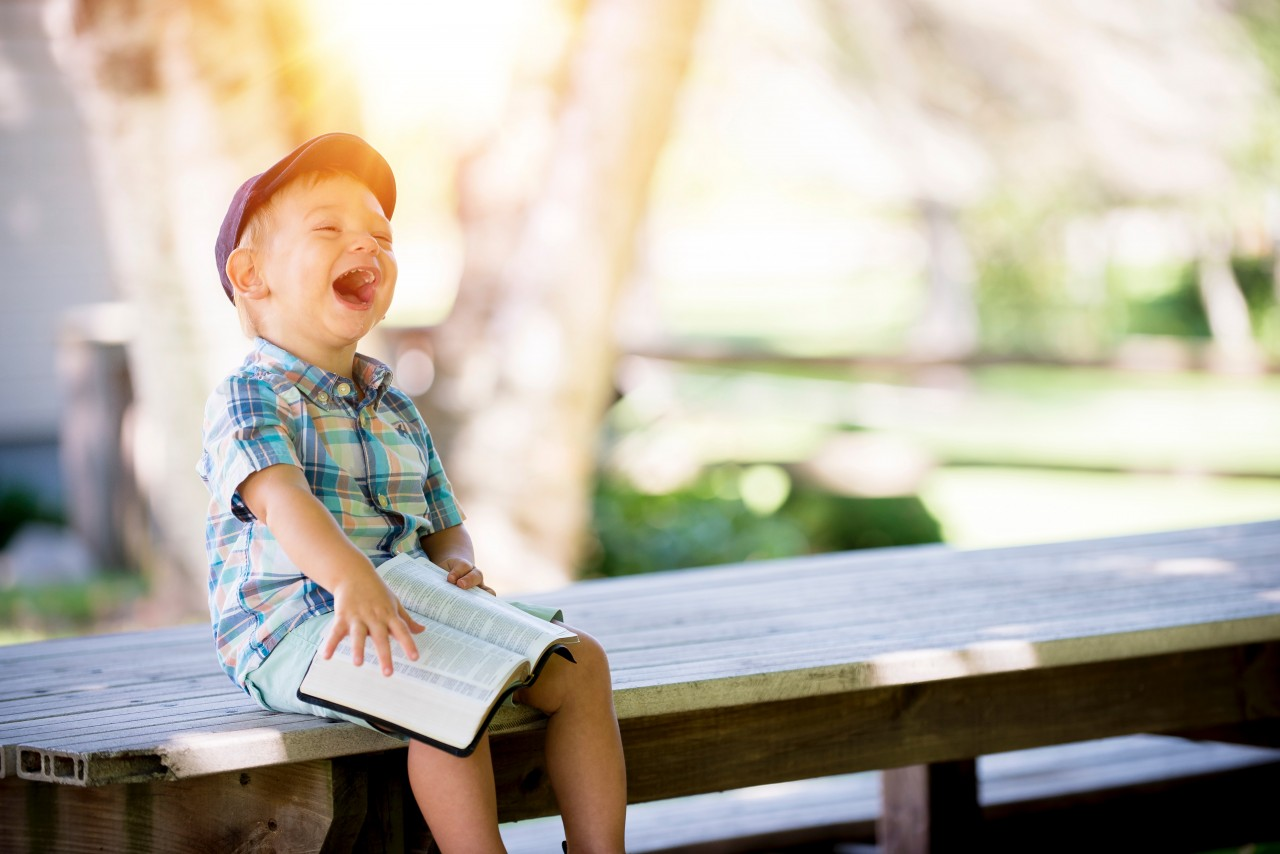 Image of a young boy wearing a checked shirt and shorts, sitting on a bench and laughing as he holds a Bible on his lap.
