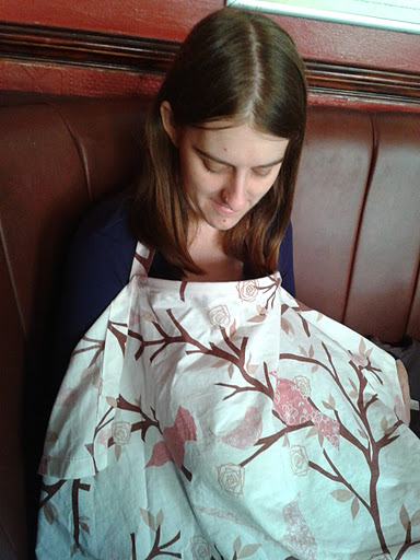 Amanda breastfeeding in public wearing a nursing cover