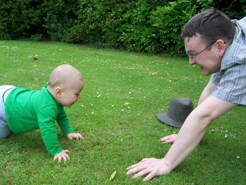 TJ and Little Man crouching laughing and playing together