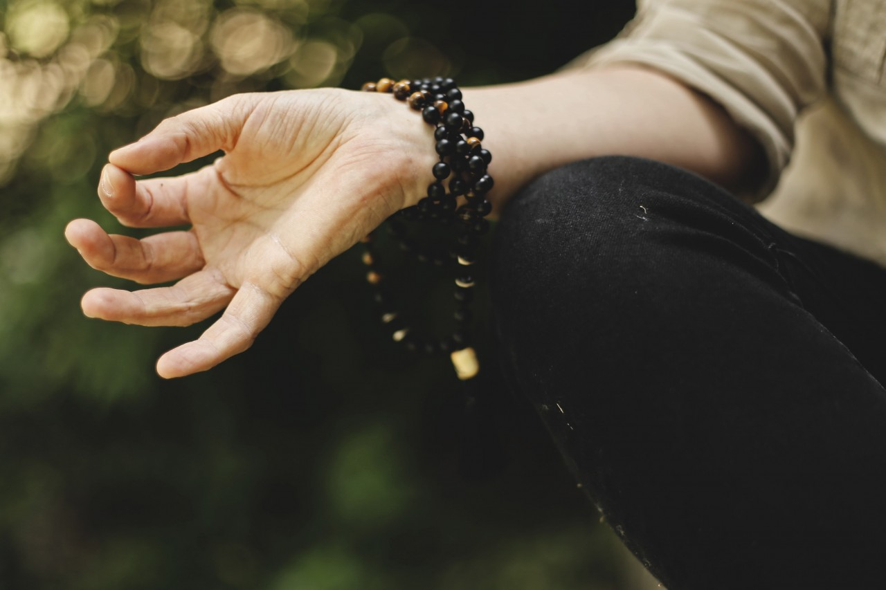 close up image of a woman's hand in a mudra with forefinger and thumb touching. She is wearing a beaded mala wrapped around her wrist, and her arm is resting on her knee.