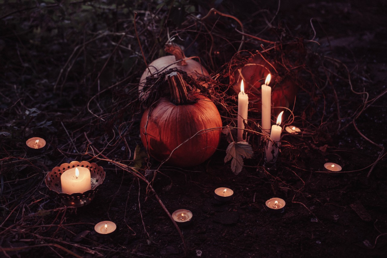 Image of two pumpkins surrounded by lit candles on a forest floor