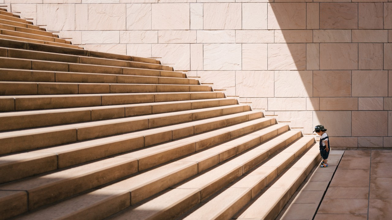 image of a toddler standing at the foot of a flight of stairs