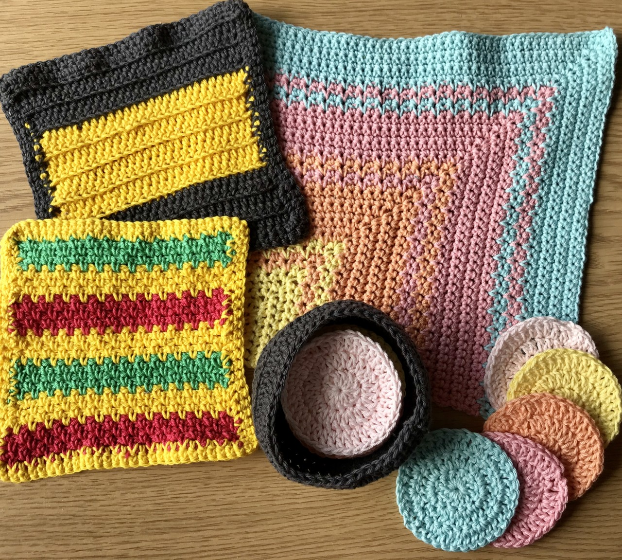 Image of multiple crocheted washcloths and reusable face pads in a basket.