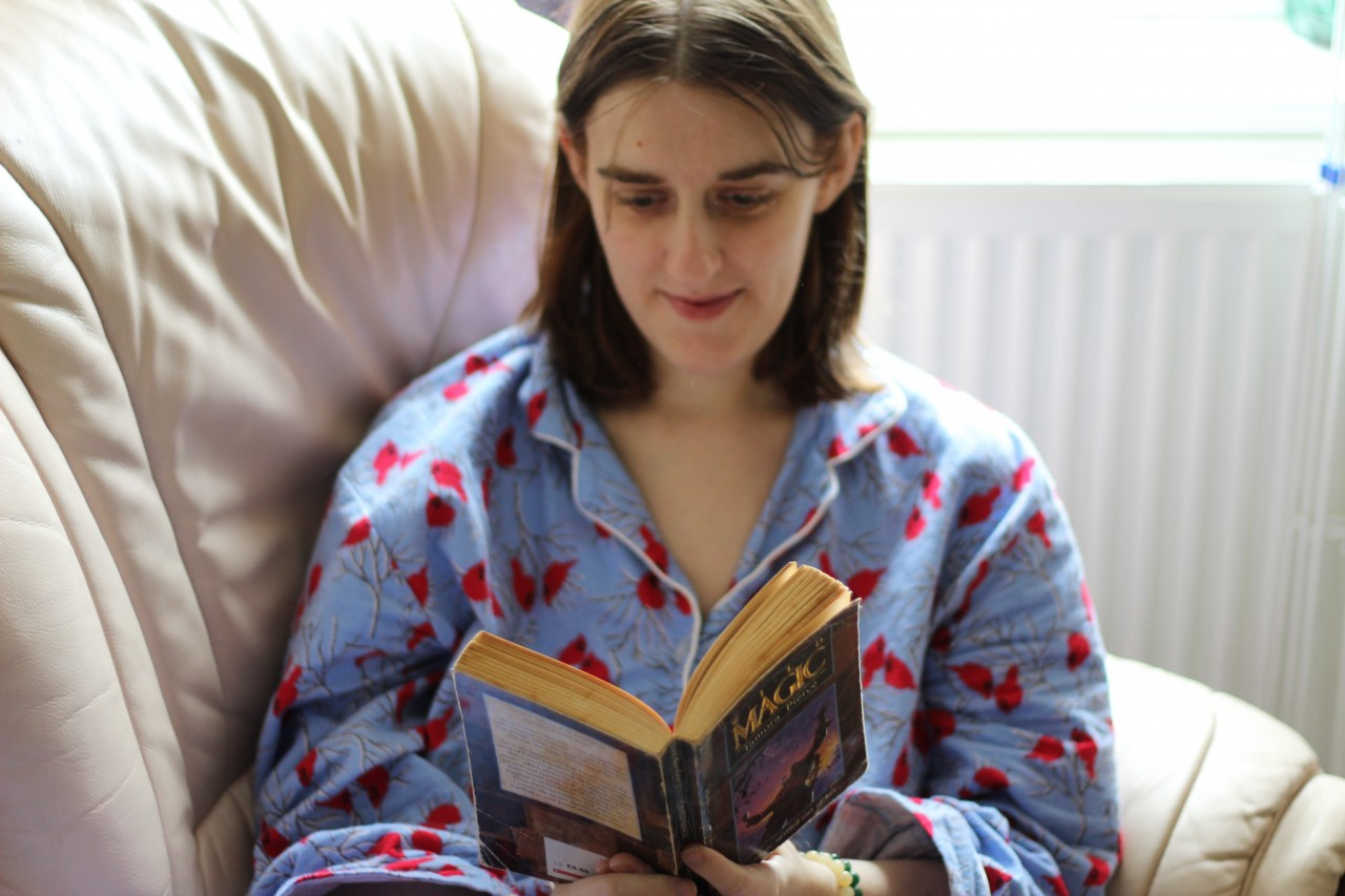 Amanda in blue pyjamas reading the book Wild Magic by Tamora Pierce