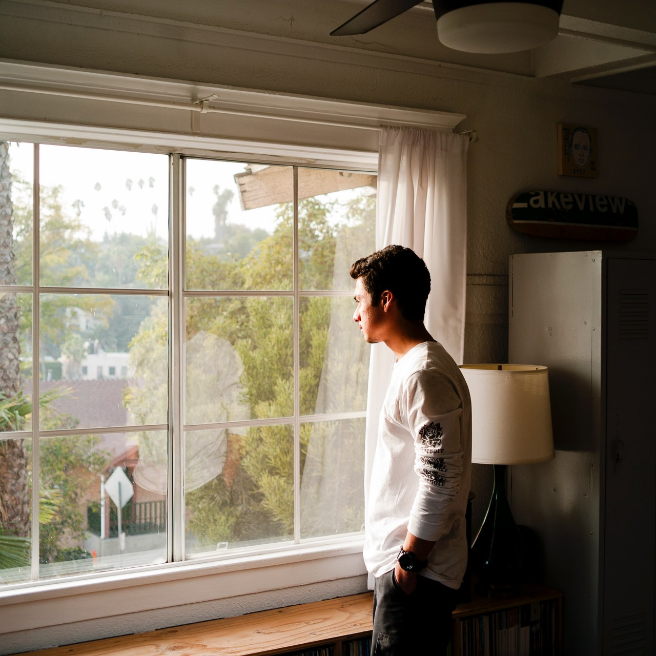 man with dark hair and white sweatshirt looking out of a window