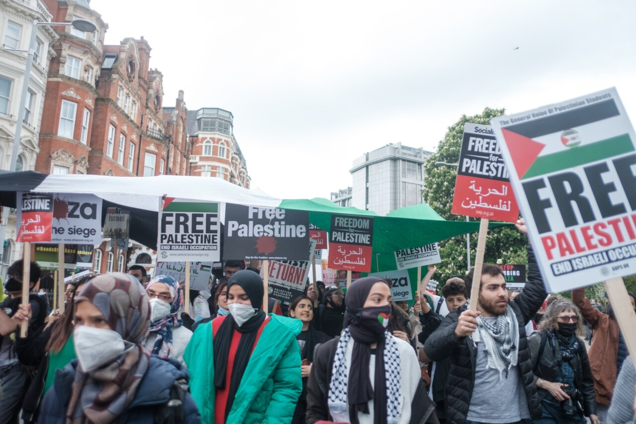 A Free Palestine March in Kensington, London. There are people wearing masks (because of Covid) and carrying placards saying Free Palestine.